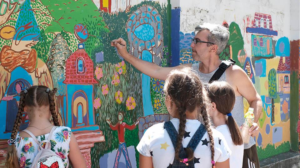 художник помогает детям расписывать стены у рынка